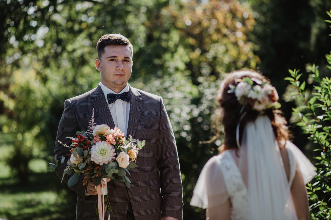 pan młody trzymający bukiet kwiatów dla panny młodej
